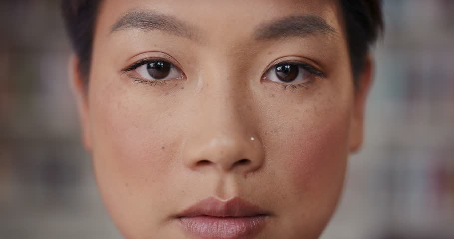 Dramatic Close up of beautiful Asian woman serious portrait slow motion soft natural light on face center crop