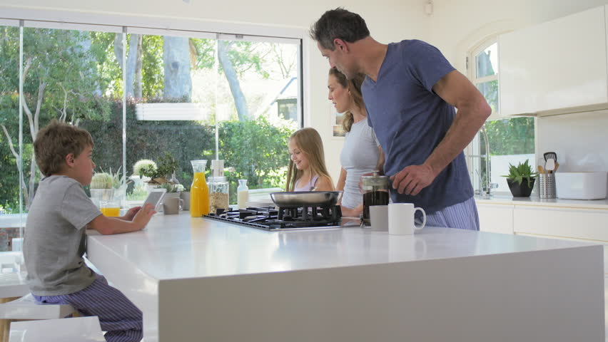 Young daughter walks into family kitchen in modern contemporary home while parents making healthy breakfast #13159448