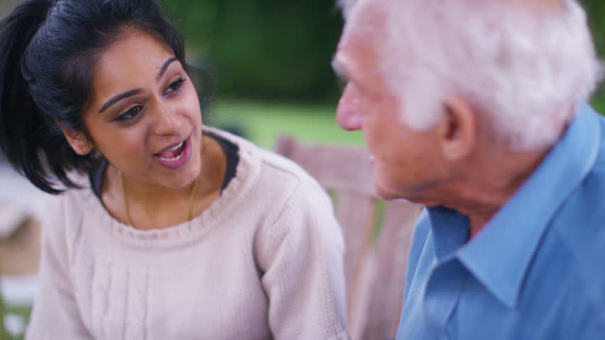 4K Caring young home support worker spending time with elderly gentleman in the garden. Shot on RED Epic
