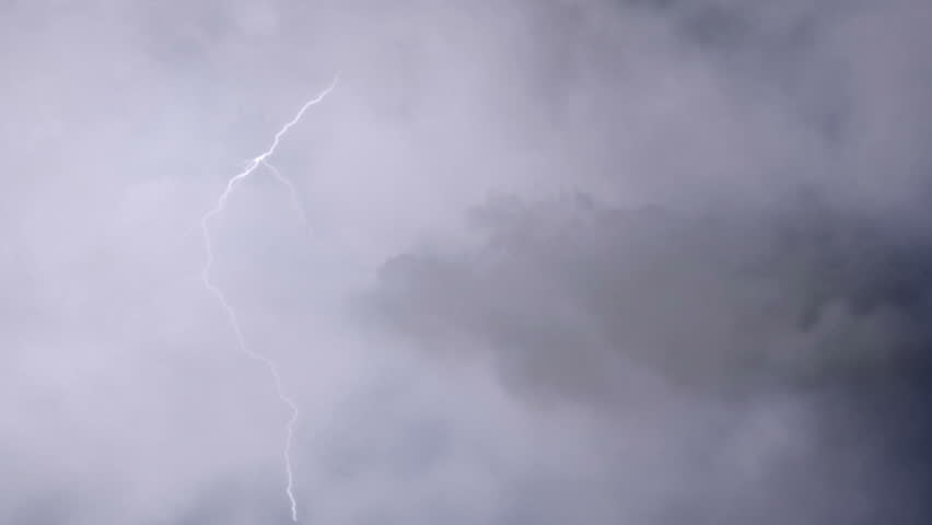 Airplane flying through heavy thunderstorm clouds, lightning bolts strike ahead. Pilot's point of view, aircraft shaking in severe turbulence. Risk of accident, the hazards of flying in the storm