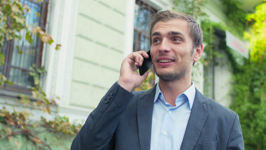 The businessman costs in the downtown and communicates with someone by phone. The man looks very happy.
