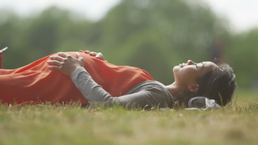 4K Happy pregnant woman relaxing in the park feels the baby kicking. Shot on RED Epic. #13178549