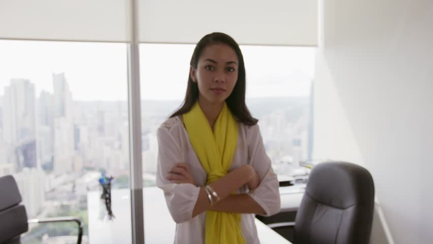 Adult businesswoman leaning on desk in modern office with beautiful sight of the city. The secretary smiles to the camera and crosses arms. Medium shot, Slow motion, steadicam shot | Shutterstock HD Video #13183967