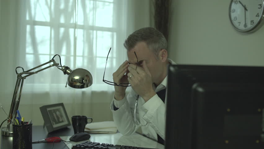 A man works at a clean desk with a computer and keyboard and mouse. He might have glasses on with a clock or medical chart in the background. The office has a window with  light outside.