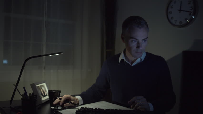 A man works at a clean desk with a computer and keyboard and mouse. He might have glasses on with a clock or medical chart in the background.  | Shutterstock HD Video #13194818