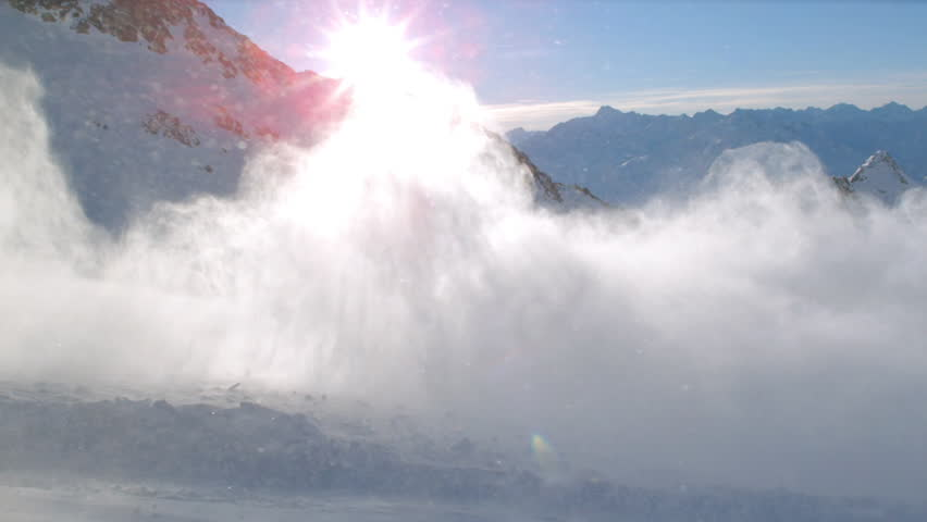 WS TS SLO MO View of snowboarder off run skiing with snowy mountains in sun ray and powdery snow / Stubai, Central Eastern Alps, Innsbruck, Austria - 01/12/2015 #13197413
