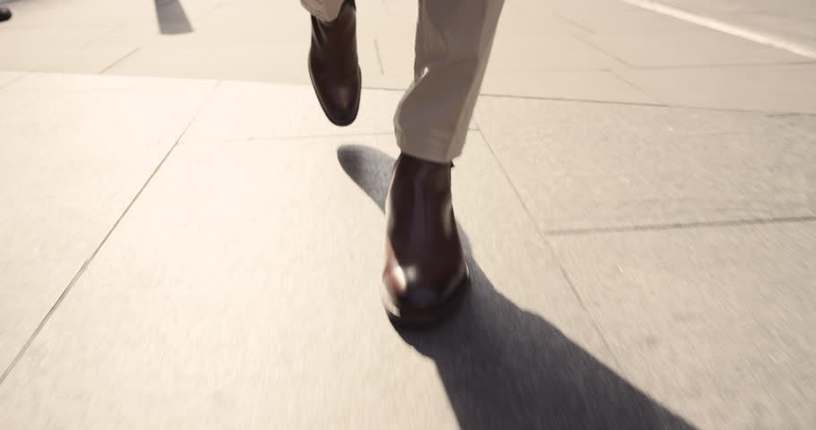 Close crop of businessman feet walking in city. Man commuting to work. Steadicam shot in slow motion with warm natural light on sidewalk | Shutterstock HD Video #13200176