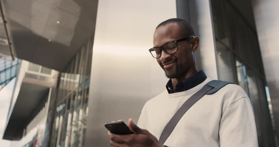 African American Man sms texting using app on smart phone in city. Handsome young businessman using smartphone smiling happy. Urban male professional commuting in his 20s | Shutterstock HD Video #13200209