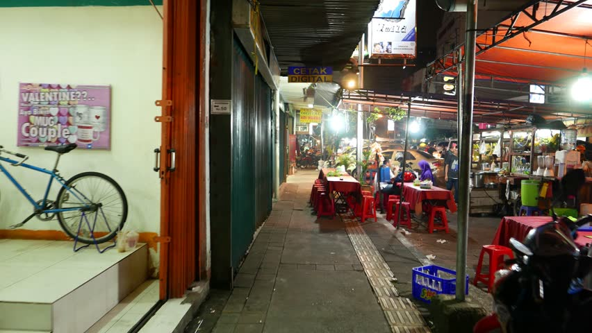 JAKARTA, INDONESIA - MARCH 09, 2015: Cheap eatery at night street, empty table and seats, Haji Agus Salim alley at dark time, busy and lively area. Glide shot, camera move along narrow sidewalk