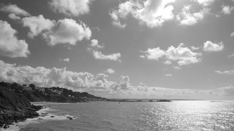 Cinemagraph of a seascape of a bay and a shore in a summer sunny day with white clouds running fast - 4k black and white motion photo.