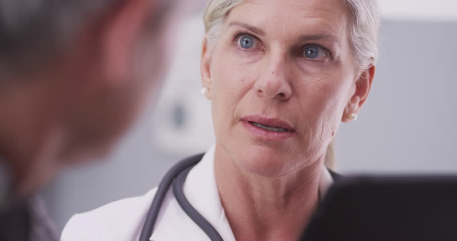 Middle-aged female doctor looking at a tablet   Shutterstock HD Video #13244279
