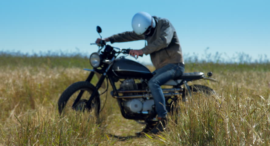 The motorcyclist getting off a retro motorcycle in the middle of the field.  | Shutterstock HD Video #13277462