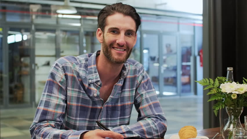 Confident smiling portrait of young creative professional having meeting with his startup team in a modern trendy cafe | Shutterstock HD Video #13300613
