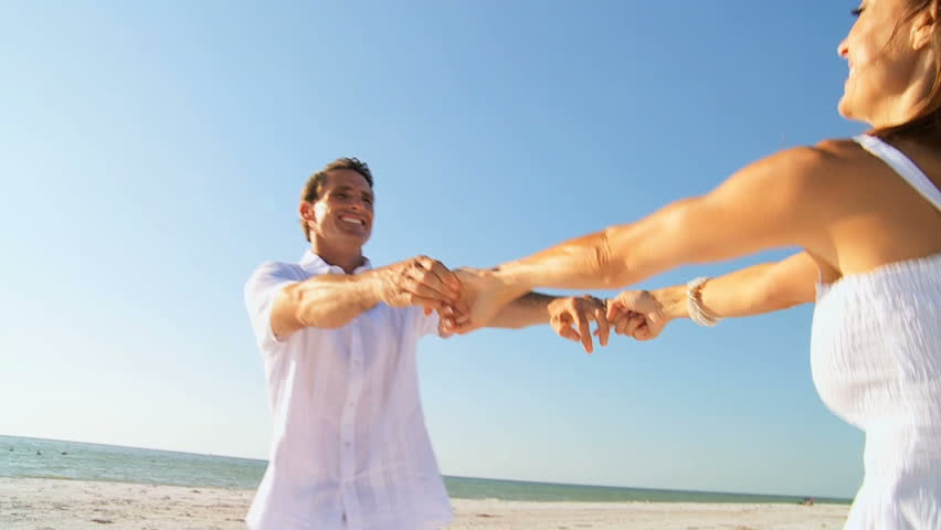 Attractive healthy couple having fun together dancing  on the beach filmed at 60FPS
