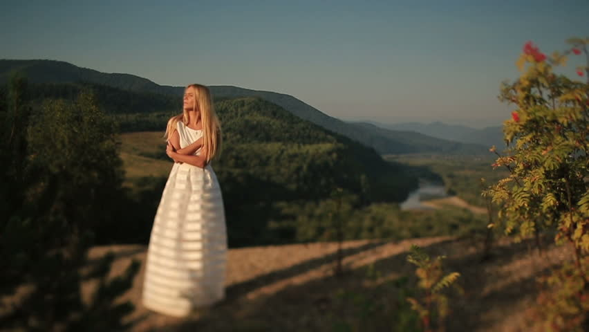 Beautiful bride in a wedding dress on a background of mountains | Shutterstock HD Video #13303052