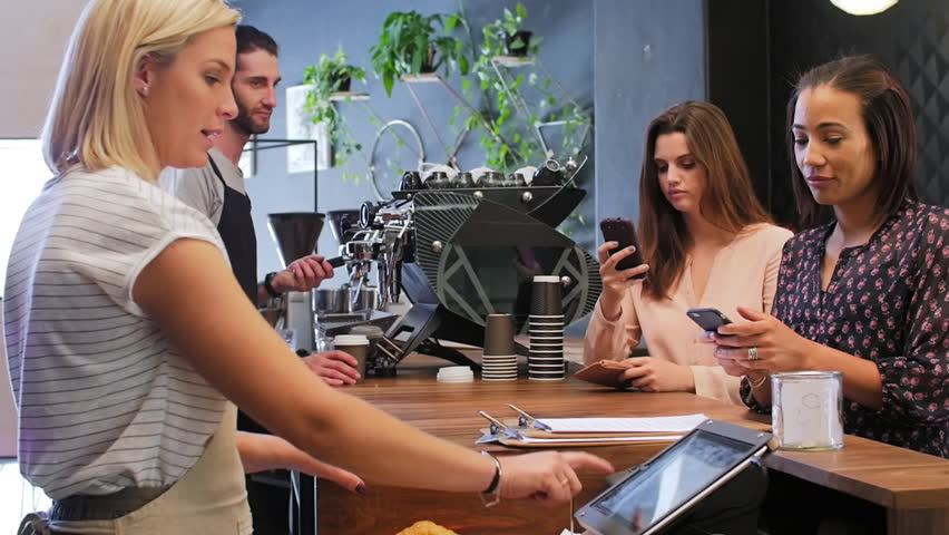 Customer makes mobile online cashless payment with cell phone, waitress behind the counter confirms payment on touch screen device in modern trendy coffee shop cafe