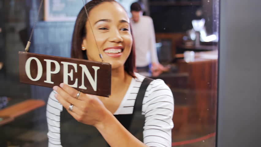 Happy mixed race woman walks up to glass door, flips over open sign for cafe opening in the morning   Shutterstock HD Video #13307618