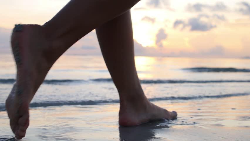 Female Feet Walking Barefoot on Sea Shore at Sunset. Slow Motion. Closeup. HD, 1920x1080.