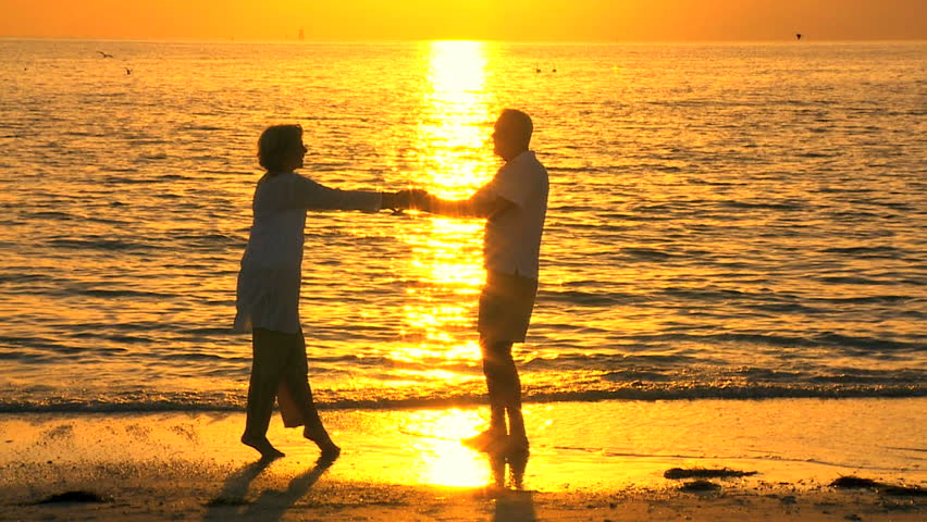 Loving senior couple enjoying a romantic sunset evening dancing together on the beach filmed at 60FPS