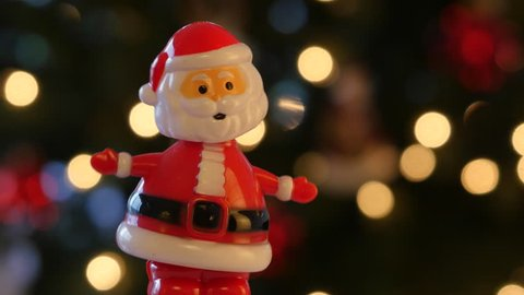 Plastic Toy Santa Claus Dancing In Front Of An Out Of Focus Christmas Tree