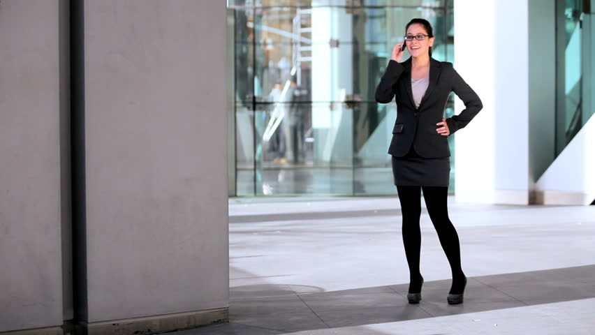 Smart young businesswoman in the atrium of a modern office building using a cell phone #1334491