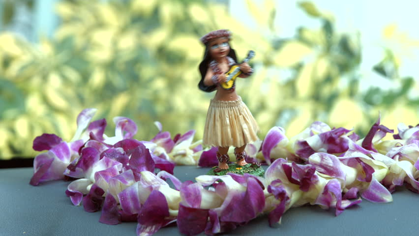 Hawaii travel car - Hula doll dancing on dashboard and lei during road trip.
