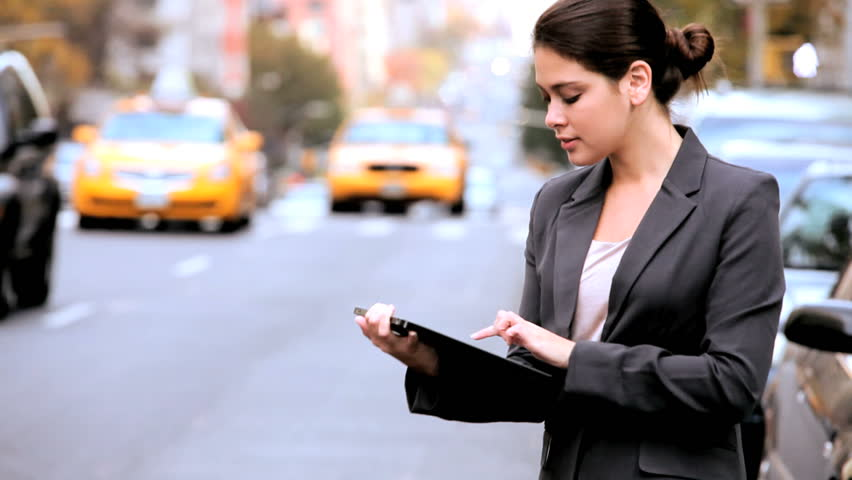 Young businesswoman in city clothes on the streets of New York working with a modern wireless tablet | Shutterstock HD Video #1334683