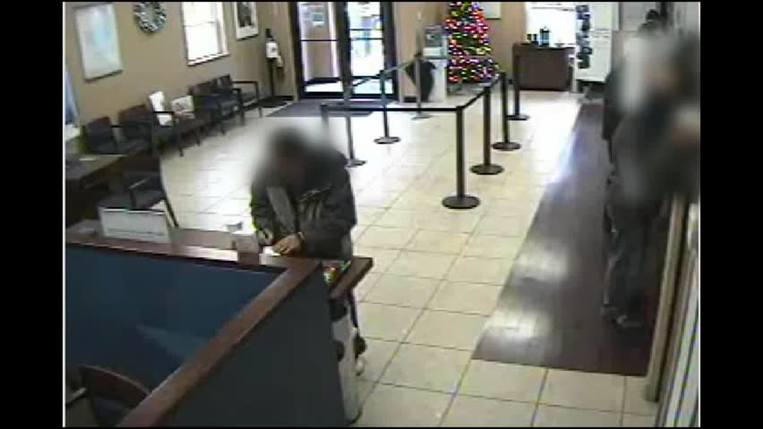 CIRCA 2010s - Surveillance camera footage of an armed robber robbing a bank.