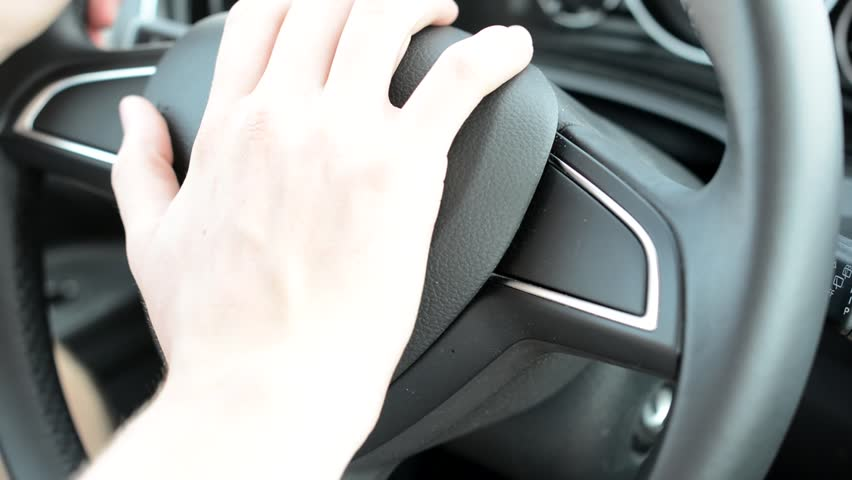 somebody pushes center of steering wheel - concept for honking