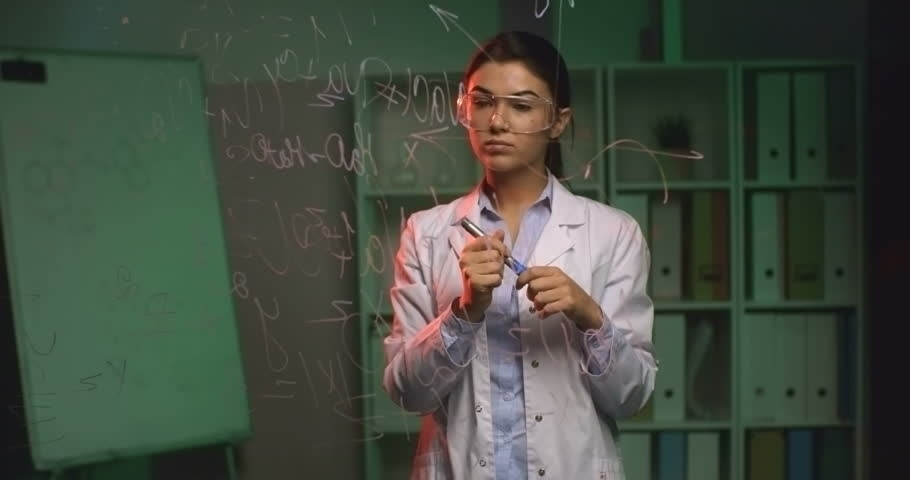 Pretty young lady in lab coat walking towards glass wall in laboratory and writing chemical equation on it #13385915