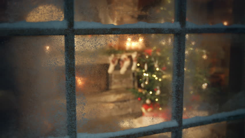 Christmas tree and fireplace scene through frozen window
