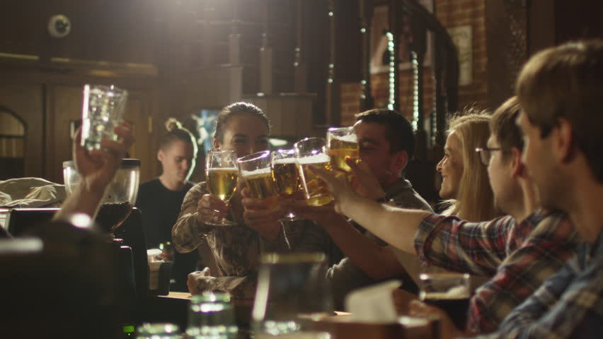 Friends do toasts, drink beer and cocktails while having a good time together at a bar. Shot on RED Cinema Camera in 4K (UHD).