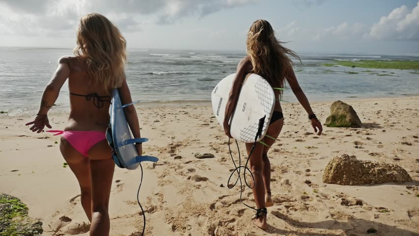 Two girls running into the ocean with their surfboards. Shot taken by a handheld gimbal in 50FPS. #13391222