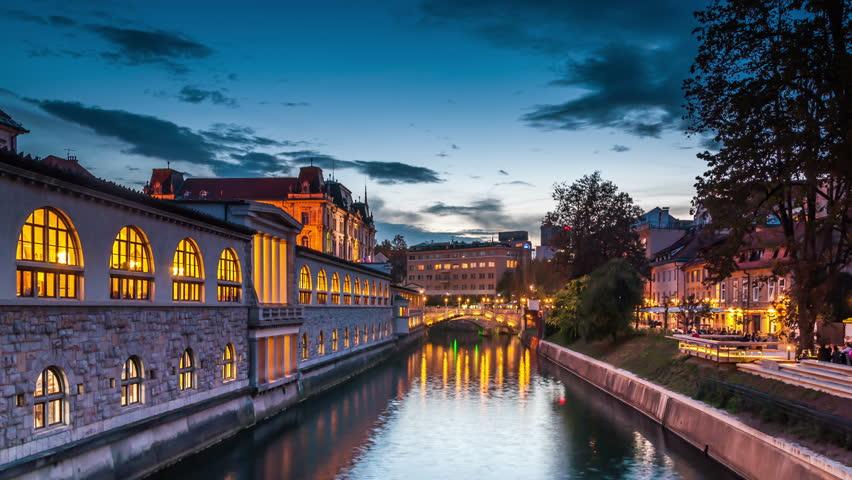 Ljubljanica river at dusk, Ljubljana, Slovenia. Day to night time lapse video. City lights switch on. Royalty-Free Stock Footage #13405547