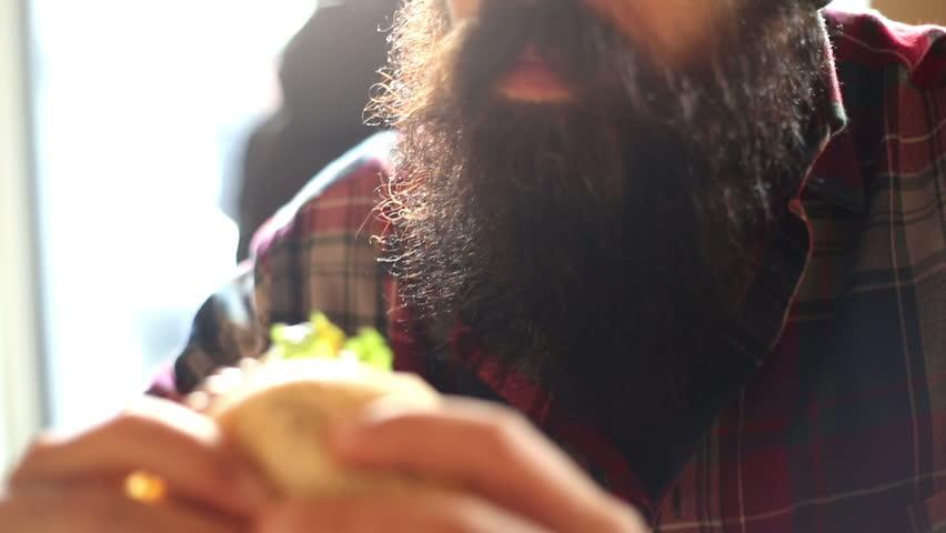 Man eating an attractive hamburger with chips and ketchup