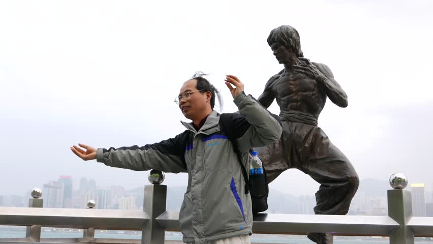 HONG KONG - FEBRUARY 18, 2015: Unidentified curious man pose against Bruce Lee statue at Avenue of Stars. Man stand in fight position, funny tourist take pictures with famous sculpture of superstar.