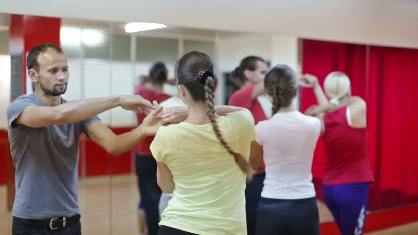 Smiling adults dancing bachata together in dance studio