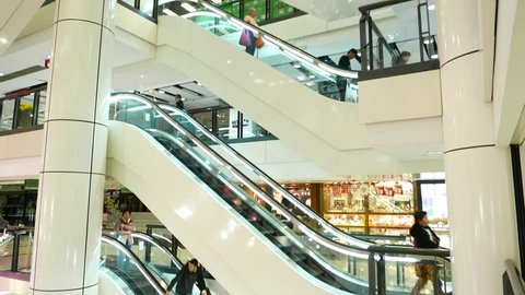HONG KONG - FEBRUARY 19, 2015: Escalators in mall, tilt up, view from open atrium side, people travelling from floor to floor, new shopping complex. White design, clear walls and open balcony.