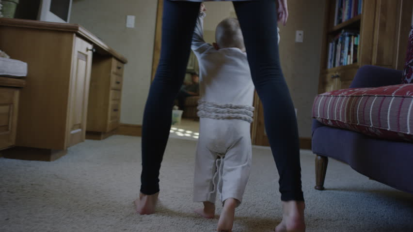 Medium tracking shot of mother helping baby daughter walk / Cedar Hills, Utah, United States #13445411