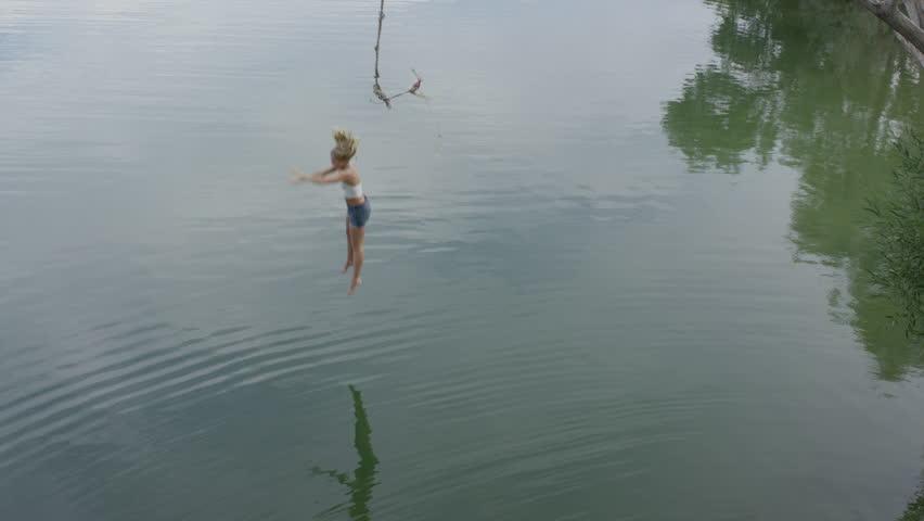 High angle wide slow motion shot of woman swinging into lake / Mona, Utah, United States