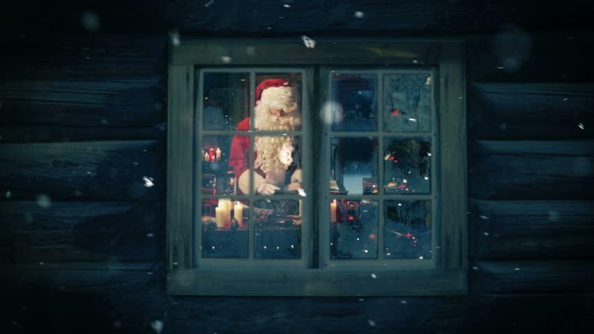 Santa seen through the frozen window preparing gifts for kids. Snowing.