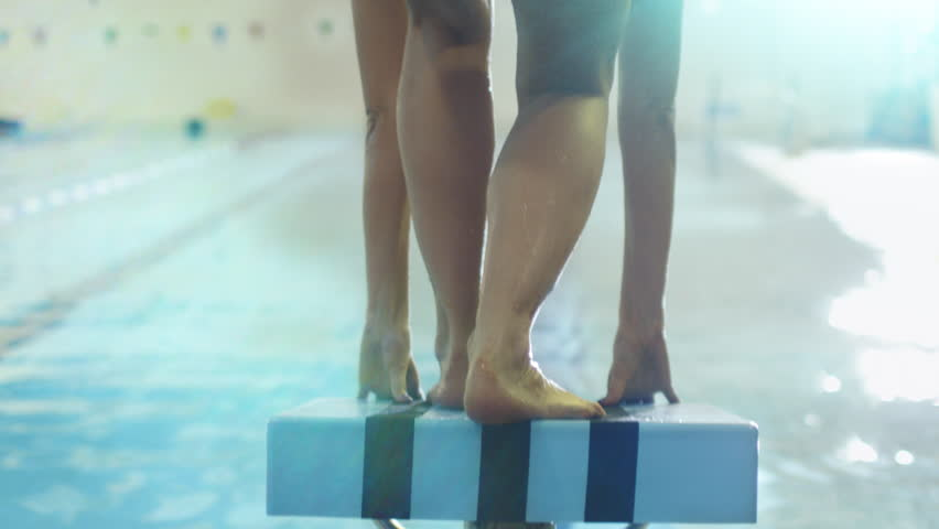 Jib Shot from Back Side of Professional Female Swimmer Preparing and Jumping Off the Starting Block into Pool. Shot on RED Cinema Camera in 4K (UHD).