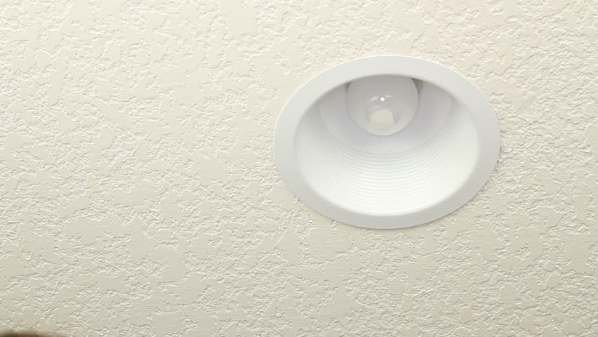 Male hand changing an old incandescent ceiling light bulb with a new energy efficient CFL lightbulb to be eco-friendly and save energy.