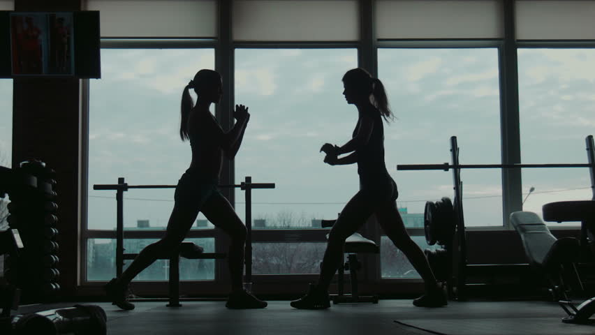 Two womans does squats and jumps exercise, wide movement shooting | Shutterstock HD Video #13463426