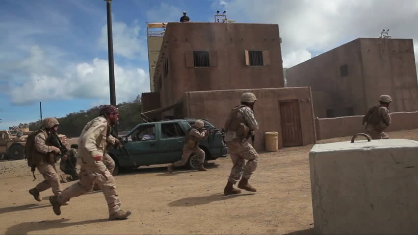CIRCA 2010s - U.S. Marines and Navy Seals conduct a terrorist firefight in a simulated Middle East village with actors playing Muslims.