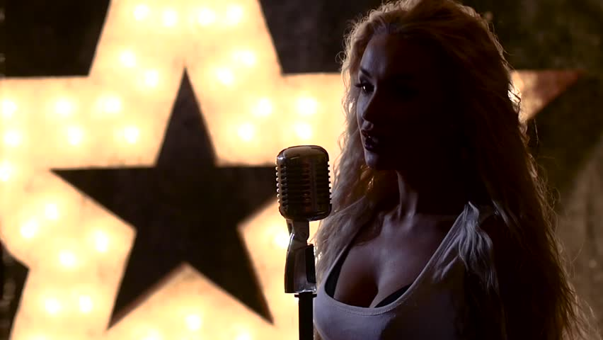 Beautiful female rocksinger with retro microphone, closed eyes singing, female jazz singer with microphone, music hall, the scene, shining star in the background, slow motion, close up, silhouette