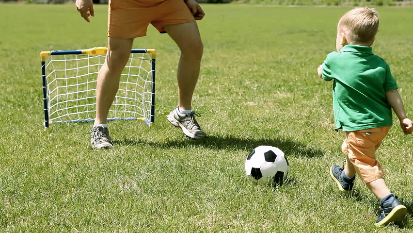 Father and son playing with soccer ball on the grass   Shutterstock HD Video #13510484