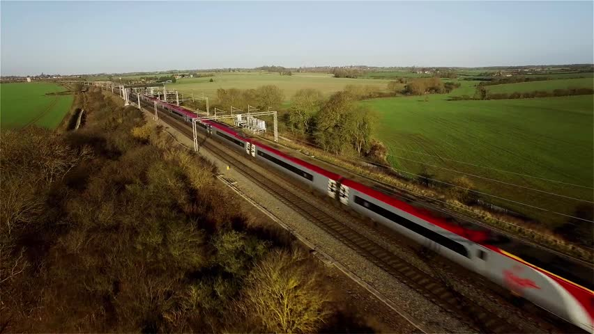 Aerial shot of a fast Virgin passenger train in the UK countryside moving towards and then passing the camera, which is tracking backwards. Plenty of cutting room either side. 4K version ID 24513560