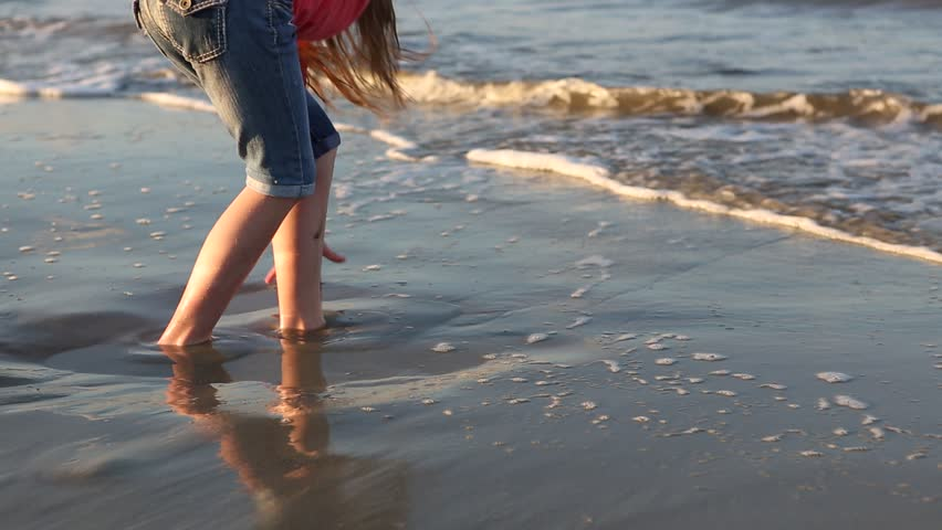 Pre-teen girl playing in sand at beach | Shutterstock HD Video #13561454