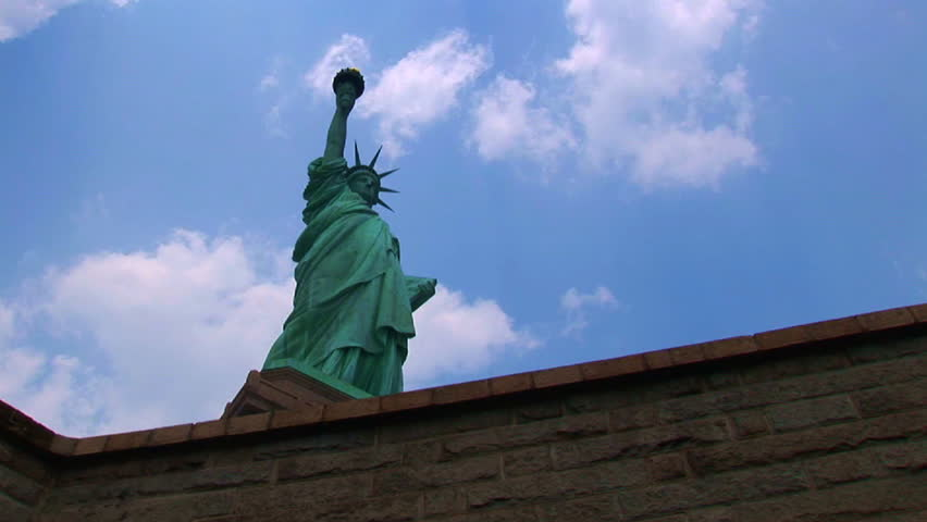 Low angle looking up at white puffs of clouds in a blue sky over the Statue of Liberty. | Shutterstock HD Video #1357114